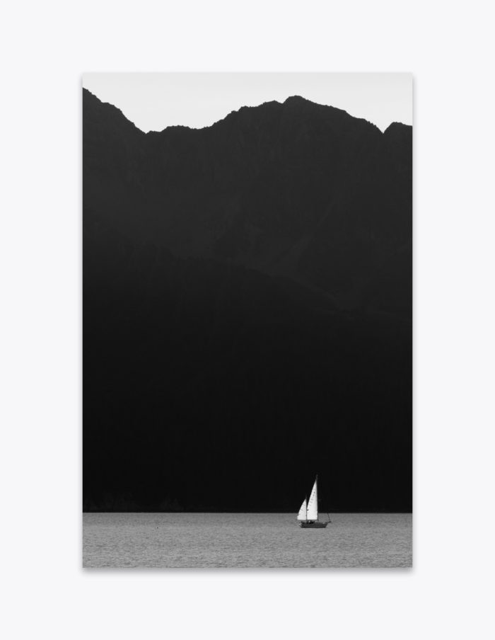 A lone sailboat drifts along the coast of the Kenai Fjords in Alaska.