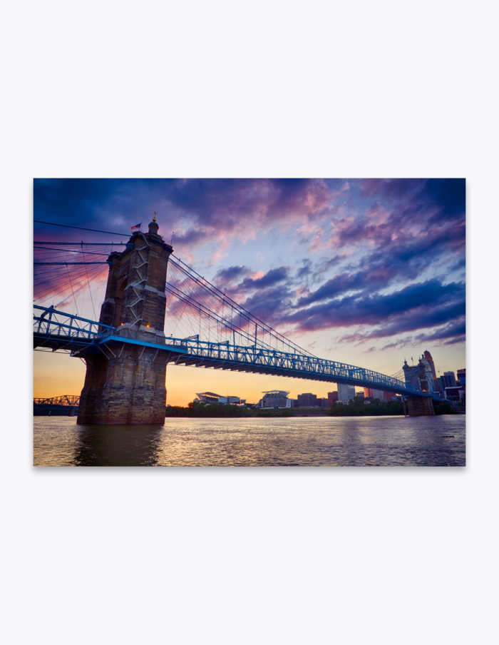 The glow of sunlight touches clouds over Roebling Bridge.